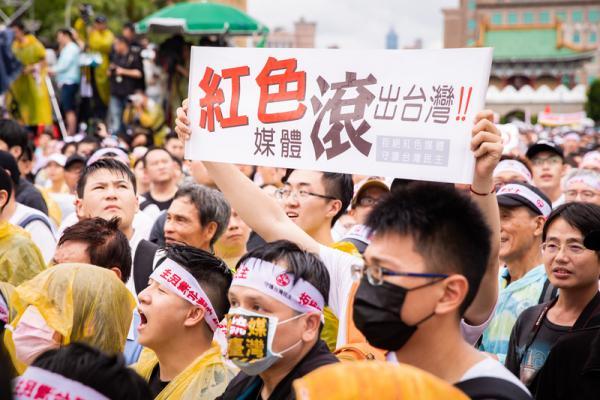 """Un manifestant brandit une pancarte avec les mots """"Médias rouges: quittez Taïwan!"""" en chinois lors d'un rassemblement à Taipei, Taiwan, le 23 juin 2019. (Image: Chen Pochou/The Epoch Times)"""