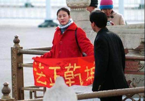 Une pratiquante de Falun Gong brandit une bannière disant «Vérité, Compassion, Tolérance» en Chine. (Image: Minghui.org)