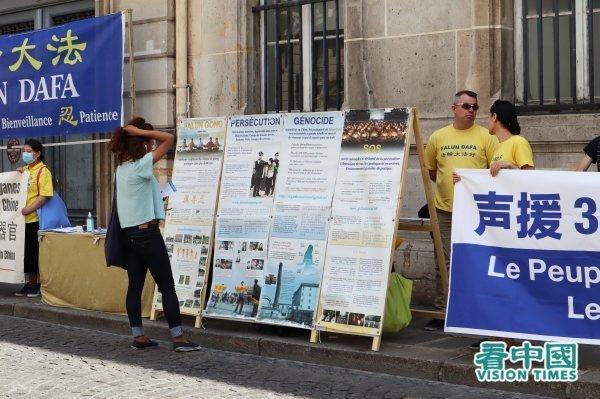 Une passante regardant le tableau d'affichage du Falun Gong. (Image : Kan Zhongguo / VisionTimes)