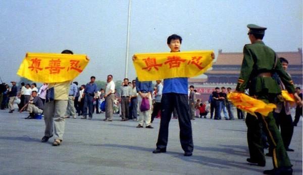 Un pratiquant de Falun Gong tient une banderole sur la place Tiananmen, sur laquelle on peut lire les caractères chinois «Vérité, Compassion, Tolérance», qui sont les principes fondamentaux de la pratique. Un policier s'approche pour l'arrêter. (Image : Falun Dafa Information Center)