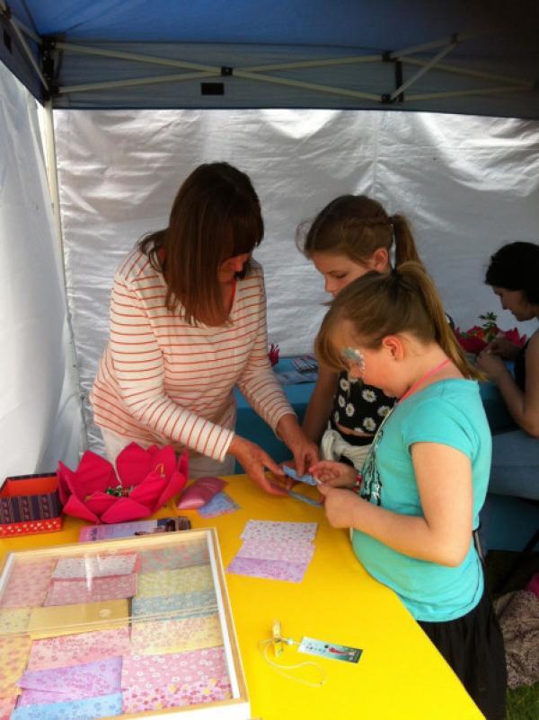 Janine apprenant aux enfants à fabriquer des fleurs de lotus en origami aux couleurs vives, lors d'un festival. (Image : Janine Rankin)