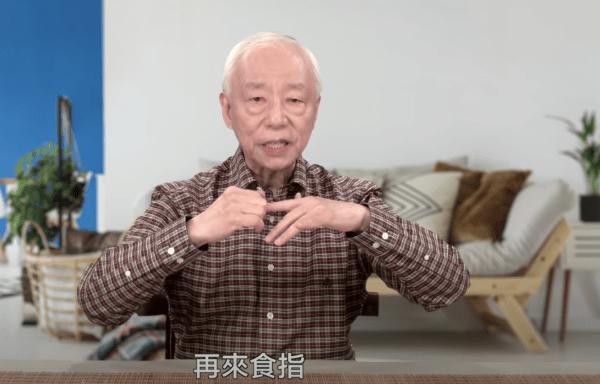 Hu Naiwen se masse l'index. (Image : Capture d'écran / YouTube)