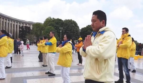 Un groupe de pratiquants de Falun Gong de France, faisant les exercices en plein air le 13 mai, lors de la Journée mondiale du Falun Dafa. (Image : Capture d'écran / YouTube)