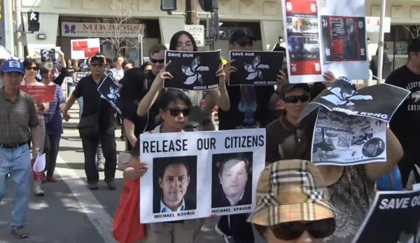 Un rassemblement canadien en soutien à Hong Kong avec des banderoles demandant la libération des citoyens canadiens Michael Kovrig et Michael Spavor, détenus en Chine. (Image : Capture d'écran / YouTube)