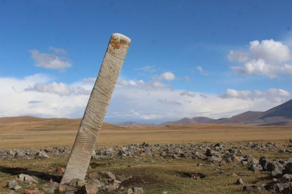 Une pierre de cerf penchée placée devant des douzaines de petits monticules de pierre contenant des sépultures de chevaux sacrifiés rituellement sur le site du monument de l'âge du bronze d'Ikh Tsagaanii Am, dans la province de Bayankhongor, en Mongolie centrale. (Image : William Taylor)