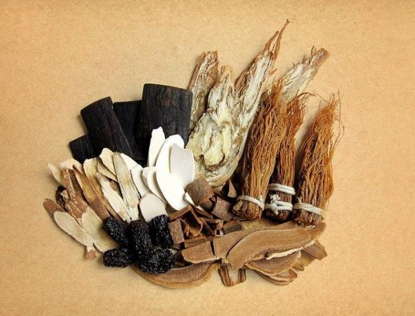 Le médecin des herbes prend un bocal sur une étagère en bois. Ensuite il place un morceau de tissu sur la table et vide le contenu sur le tissu. (Image :vivi14216/Pixabay)