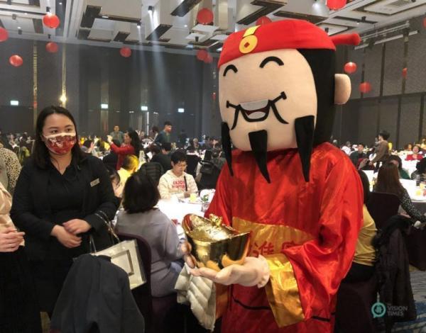 Un membre du personnel de l'hôtel agissant en tant que « Dieu de la richesse » distribue des bonbons aux clients du restaurant. (Image: Billy Shyu / Vision Times)