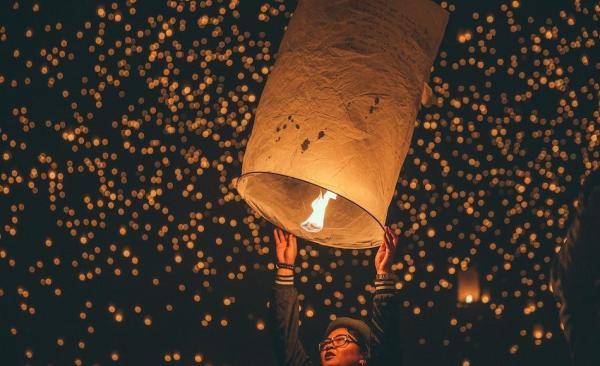Lâcher une lanterne dans le ciel avec des souhaits écrits dessus pour la nouvelle année à venir. (Image :unsplash.com/ @Austin Neill)
